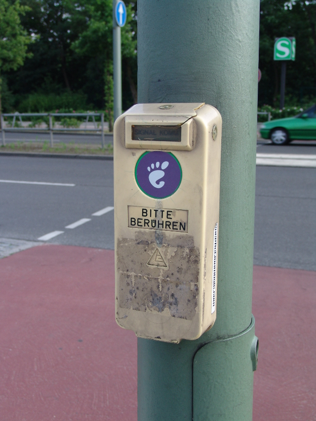 "Gnome sticker on a crosswalk button, above it says in German ""please touch"""